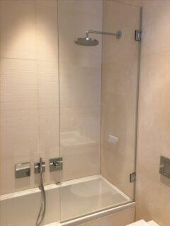 Custom made glass shower screen over bath with hinge